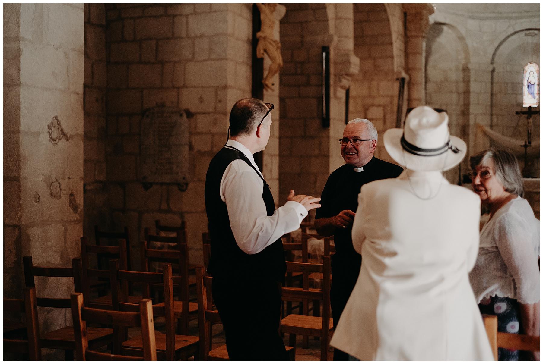 prête et marié discutent dans l'église de monteton